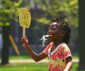 """A kid holding up a sign saying """"Child Care Now"""""""